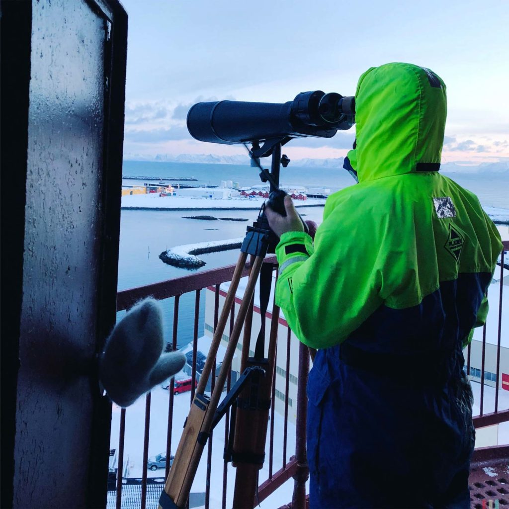 Winter Whale Watching in Norway: A guide looking for whale at the lighthouse in Andenes.
