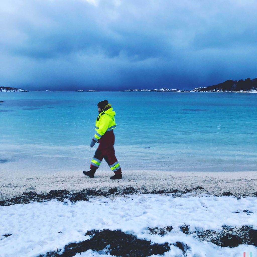 Winter Whale Watching in Norway: Theresa walking on the beach on Senja Island.